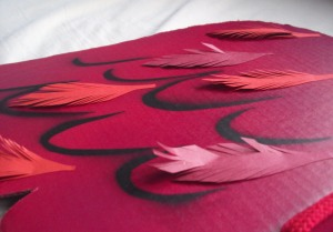paper feathers on red bird wings